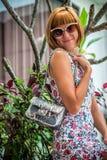 Vestido de la flor de la mujer joven del encanto que lleva que presenta con el bolso hecho a mano de lujo del pitón del snakeskin Foto de archivo libre de regalías