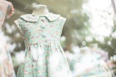 Vestido de la moda de la chica joven en ventana de la tienda de la moda del childrenswear Fotografía de archivo libre de regalías