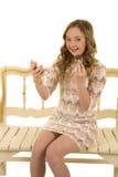 Vestido de la muchacha con el maquillaje que se sienta en un banco Foto de archivo