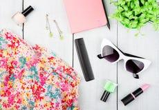 vestido de la mujer, libreta, gafas de sol y otros accesorios en el escritorio de madera blanco Fotografía de archivo