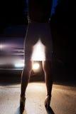 Vestido de la parte posterior de la mujer a la luz de los coches de las linternas Foto de archivo libre de regalías