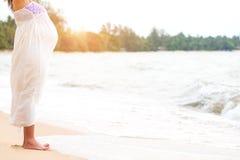 Vestido de maternidade branco do desgaste de mulher gravida que está na praia e fotografia de stock royalty free