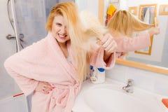 Vestido de molho vestindo chocado da mulher que escova seu cabelo foto de stock royalty free