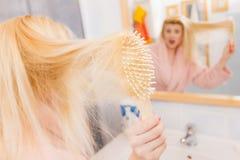 Vestido de molho vestindo chocado da mulher que escova seu cabelo fotografia de stock royalty free