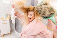 Vestido de molho vestindo chocado da mulher que escova seu cabelo imagens de stock