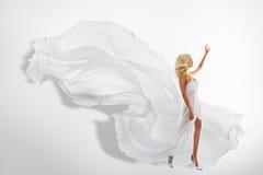 Vestido de ondulação do branco da mulher, mostrando a mão acima, voando a tela de seda Fotografia de Stock
