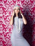 Vestido de plata que lleva y sombrero de la mujer hermosa que presentan en fondo del ornamentall Fotos de archivo