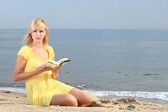 Vestido del amarillo de la muchacha del libro de lectura de la mujer Fotografía de archivo