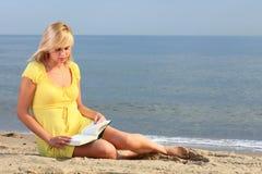 Vestido del amarillo de la muchacha del libro de lectura de la mujer Imagenes de archivo