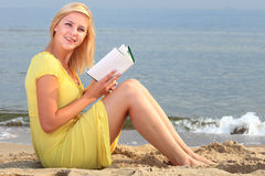 Vestido del amarillo de la muchacha del libro de lectura de la mujer Foto de archivo libre de regalías