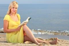 Vestido del amarillo de la muchacha del libro de lectura de la mujer Imágenes de archivo libres de regalías