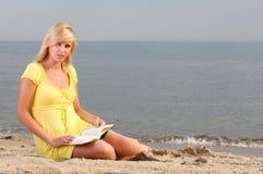 Vestido del amarillo de la muchacha del libro de lectura de la mujer Foto de archivo