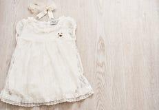 Vestido del cordón del bebé del vintage y venda blancos del arco en Gray Wodden Background ligero Visión superior, espacio de la  Foto de archivo