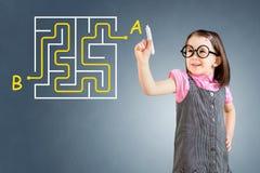 Vestido del negocio de la niña que lleva linda y encontrar la escritura de la solución del laberinto en el whiteboard Fondo para  Foto de archivo libre de regalías