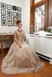 Vestido del vintage de la muchacha que se sienta Fotos de archivo libres de regalías