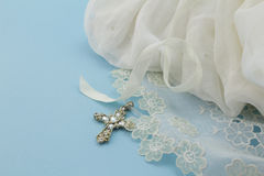 Vestido do batismo do bebê do vintage no fundo azul com cruz Imagens de Stock Royalty Free