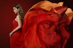Vestido do voo da mulher, modelo de forma elegante no vestido vermelho de vibração imagem de stock royalty free