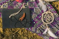 Vestido, dreamcatcher e livro encontrando-se na terra seca Estilo do moderno Imagem de Stock Royalty Free
