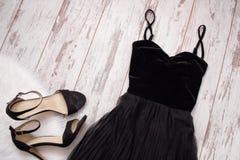 Vestido e sapatas pretos de noite em um fundo de madeira Conceito da forma Vista superior imagens de stock