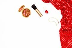 Vestido, esmalte de uñas, pulsera de la perla y cepillo rojos femeninos del maquillaje en el fondo blanco Concepto mínimo de la b Imagenes de archivo