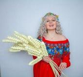 Vestido hermoso de Chubby Blonde Girl In Red con el ramo del trigo en fondo sólido del estudio blanco foto de archivo libre de regalías