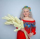 Vestido hermoso de Chubby Blonde Girl In Red con el ramo del trigo en fondo sólido del estudio blanco foto de archivo