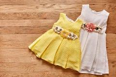 Vestido hermoso dos para las niñas en fondo de madera Imagen de archivo libre de regalías