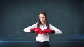 Vestido hermoso joven de la mujer en la camisa blanca que se coloca en actitud del combate con los guantes de boxeo rojos Concept Fotografía de archivo libre de regalías