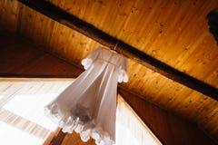 Vestido leve e inverso da noiva que pendura em um gancho fotografia de stock