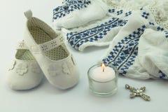 Vestido, montantes, cruz e vela do batismo no fundo branco Foto de Stock Royalty Free