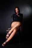 Vestido moreno atractivo del negro del desgaste que se sienta en la silla de cuero Foto de archivo