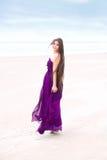 Vestido púrpura que lleva adolescente en la playa que mira detrás sobre hombro Fotos de archivo libres de regalías