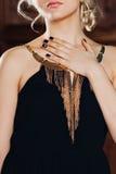 Vestido preto elegante com joia do ouro em uma menina loura nova sensual bonita com cabelo encaracolado longo e os brincos na mod imagens de stock royalty free