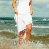 Vestido que lleva de la mujer rubia que camina en agua Imagen de archivo