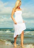 Vestido que lleva de la mujer rubia que camina en agua Fotografía de archivo