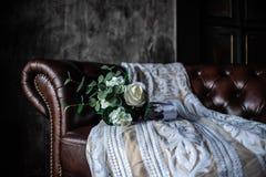Vestido que se casa hermoso de la novia presentada cuidadosamente en una silla de cuero marrón con un ramo blanco fotografía de archivo libre de regalías