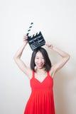 Vestido rojo de la mujer asiática hermosa joven que sonríe con clapperboard fotos de archivo