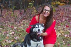 Vestido rojo de la mujer joven que juega con un perro en un parque Foto de archivo libre de regalías
