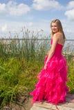 Vestido rojo del baile de fin de curso de la muchacha por las cañas altas Imágenes de archivo libres de regalías