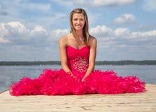 Vestido rojo del baile de fin de curso de la muchacha que se sienta en muelle Imagen de archivo