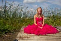 Vestido rojo del baile de fin de curso de la muchacha que se sienta en muelle Imágenes de archivo libres de regalías