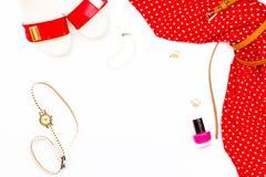 Vestido rojo femenino, pulsera de la perla, zapatos, relojes, esmalte de uñas y pendientes con clip en el fondo blanco Fotos de archivo libres de regalías