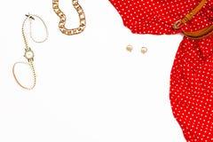 Vestido rojo para mujer, reloj, pendientes, y decoración en el fondo blanco Concepto femenino mínimo de la belleza Endecha plana Foto de archivo