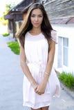 Vestido rosado moreno hermoso, colocándose en la calle, un día soleado brillante, estilo de la moda, vida urbana, presentación, m Fotografía de archivo libre de regalías