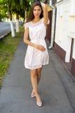 Vestido rosado moreno hermoso, colocándose en la calle, un día soleado brillante, estilo de la moda, vida urbana, presentación, m Imagen de archivo libre de regalías