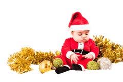 Vestido serio del bebé como santa que mira las chucherías imagen de archivo libre de regalías