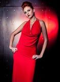 Vestido vermelho da mulher da forma com pouco saco Fundo da parede do metal Foto de Stock