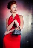 Vestido vermelho da mulher da forma com pouco saco Fundo da parede do metal Imagem de Stock