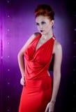Vestido vermelho da mulher da forma com pouco saco Fundo da parede do metal Fotografia de Stock