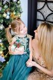 Vestido vestindo da mãe caucasiano nova e da filha pequena que está a árvore de Natal próxima imagem de stock